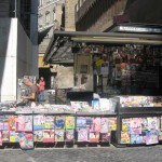 A newspaper stand right next to the arch leading to Via di Porta Angelica